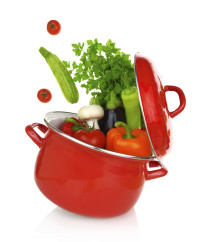 Colorful vegetables coming of a red cooking pot